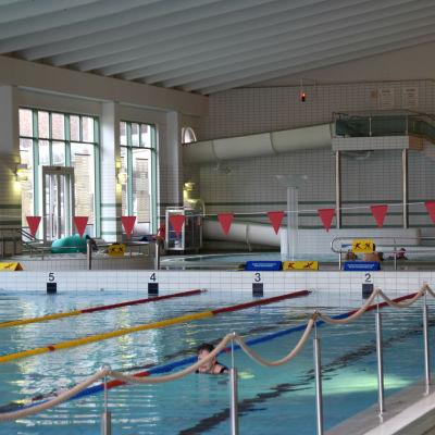 En simhall där några motionärer simmar.