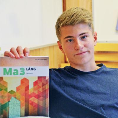 Axel håller upp matematikboken och ler. Tittar in i kameran. Har blå skjorta.
