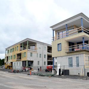 Två trevåningshus med bostäder som håller på att byggas.