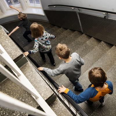 Kuvassa oppilaat kulkevat jonossa portaita kohti ruokalaa.
