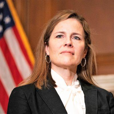Amy Coney Barrett tummassa asussa, valkoisessa kauluspaidassa. Taustalla huoneessa näkyy Yhdysvaltain lippu.