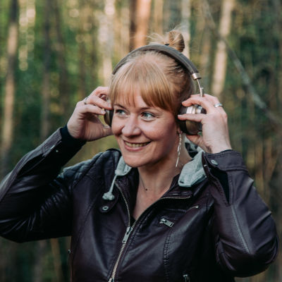Nainen kuuntelee kuulokkeilla ulkoilmassa.