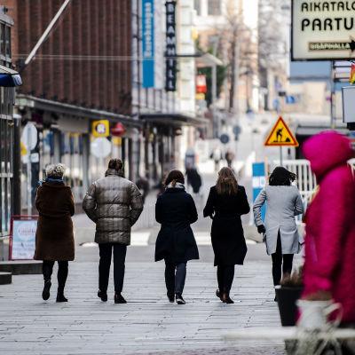Kuvassa viisi ihmistä kävelee poispäin kamerasta.