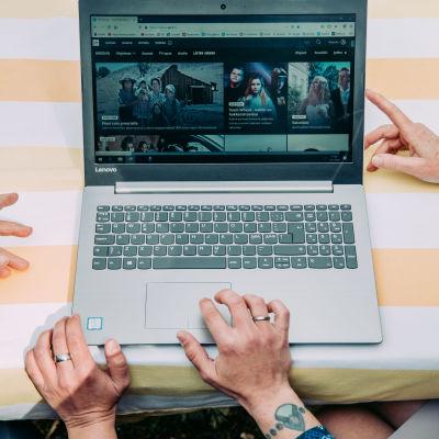Joukko ihmisiä kannettavan tietokoneen ääressä, koneen näytöllä Yle Areena.