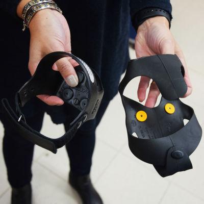 En bild på ett par händer som håller i svarta halkskydd av två olika modeller. En sitter på hälen och den andra på hela skon.