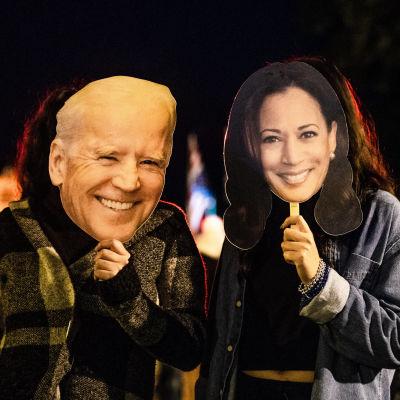 Kaksi Bidenin ja Harrisin vaalivoiton juhlijaa pitävät kasvoillaan Bidenin ja Harrisin naamareita Washingtonissa.