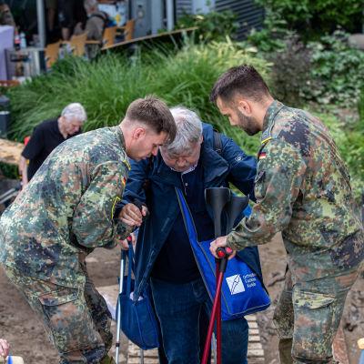 Kaksi sotilasta taluttaa vanhusta.
