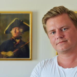 en bild av jonas ansikte och axlar. han bär en vit t skjorta och i bakgrunden ser man tavlor av regenter.