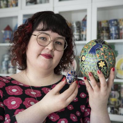 Hanna Lintu esittelee koristeelliseksi maalattua strutsinmunaa ja kananmunaa.