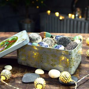 Pieniä koristeltuja kiviä metallirasiassa.