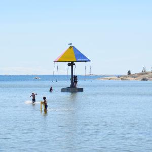 En bild på havet. I mitten av bilden finns en karusell som snurrar i vattnet. barn åker i karusellen och barn springer i grunt vatten. Strandidyll.