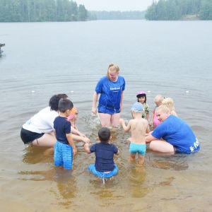 Ett tiotal barn och några vuxna kvinnor plaskar och leker  i vattnet vid en strand.