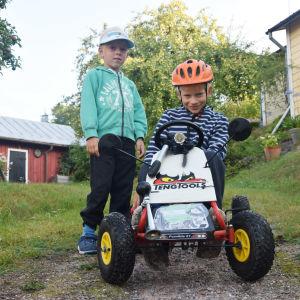 En pojke sitter på en lådbil. Brevid honom står hans bror. Pojkarna sitter i en backe på en gård med äppelträd.
