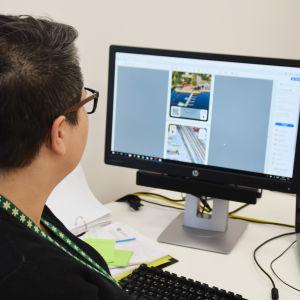 En bild på en kvinna som tittar på en datorskärm.