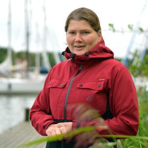 Kvinna i röd jacka står ute framför båtar som lagt till vid en brygga.