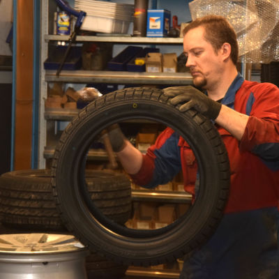Mekaniker arbetar med ett däck.