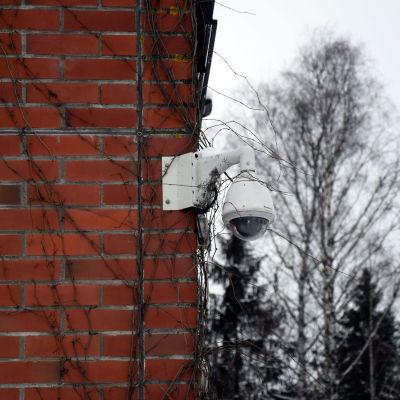 Rödtegelvägg med övervakningskamera.