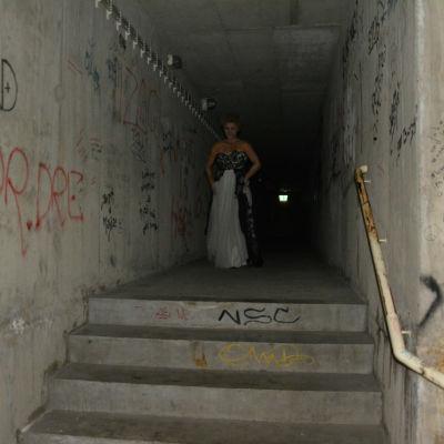 En mörk betonggång med vita frun en bit bort i gången.