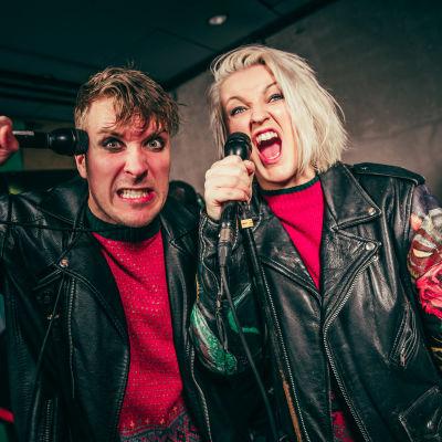 YleX Aamun Köpi ja Ylex Iltapäivän Jenspa laulamassa punk-henkiset vaatteet ja meikit yllään.
