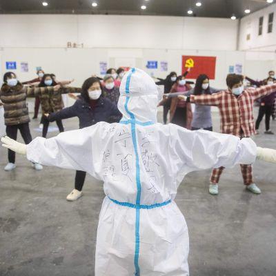 Medicinsk personal leder gruppgymnastik bland människor som smittats av coronaviruset och som tagits in på ett tillfälligt sjukhus och som uppvisar milda symptom av viruset. Bilden är tagen i Wuhan på måndagen.