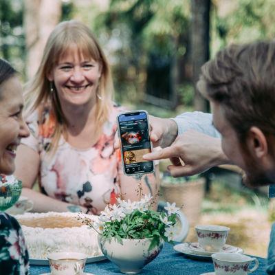 Seurue ruokapöydän ääressä puutarhassa katselee Yle Areenaa kännykältä.