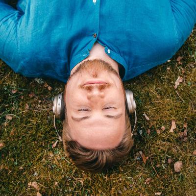 Mies makaa selällään maassa ulkoilmassa ja kuuntelee kuulokkeilla.