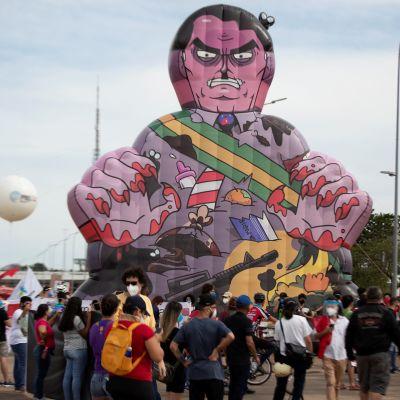 Demonstration i Brasilien. Människosamling och en stor uppblåsbar figur som ska föreställa president Bolsonaro.
