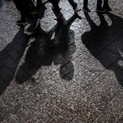 En reflektion av unga personer i asfalten. Personernas skor syns på bilden.