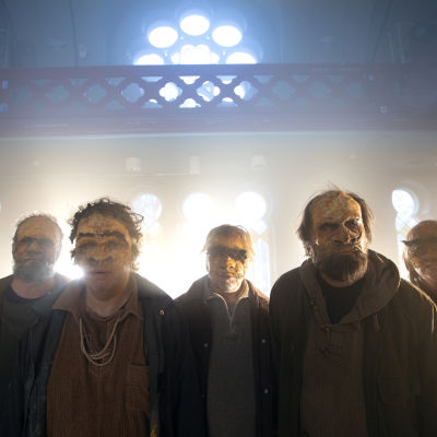 Fem skådespelare med masker i ansiktet står i motljus i en gammal kyrksal.