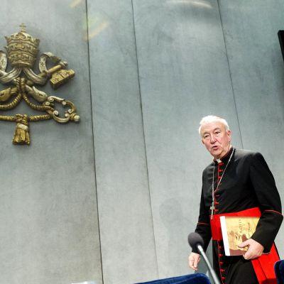 Kardinaali Nichols kulkee mustassa asussa. Seinällä on Vatikaanin vaakuna.