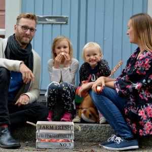 Familjen sitter på trappan och äter äpple