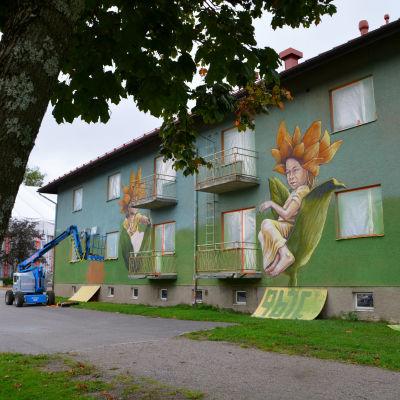 En bild på huset. Mossgrönaväggar. Barn som sitter i kronblad.
