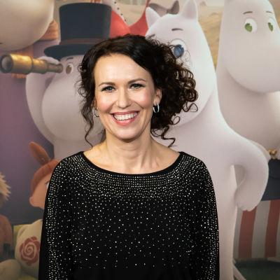 Gutsy Animations -tuotantoyhtiön luova johtaja Marika Makaroff poseeraa hymyillen kohti kameraa muumiaiheisen kuvan edessä.
