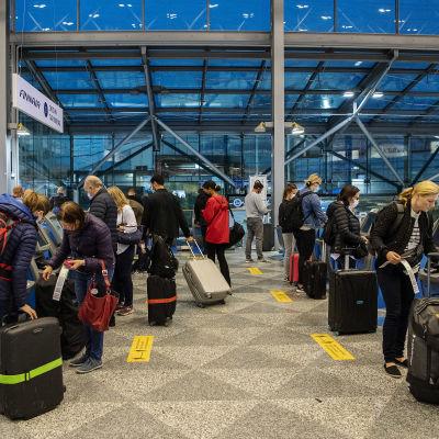 Resenärer med kappsäckar står vid Finnairs check-in-kiosker på Helsingfors-Vanda flygplats.