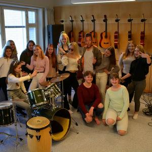 Många tjejer samlade runt trummorna. Gitarrer hänger bak på väggen.