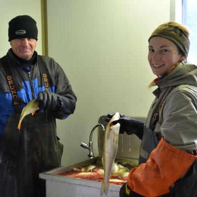 Marie Kellgren håller i en fisk framför diskhon, likaså Viking Kellgren.
