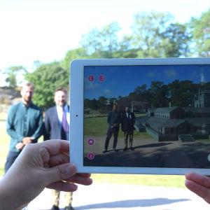 Två män står bredvid varandra och fotograferas med hjälp av en mobilplatta. De befinner sig i en miljö med förstärkt verklighet.