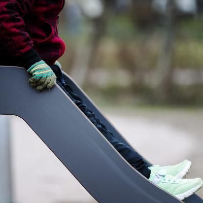 Ett barn sitter i en rutschkana.