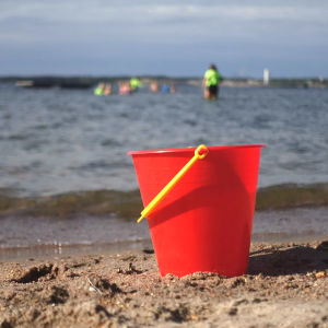 En röd plasthink på en sandstrand med barn som simmar i vattnet i bakgrunden.