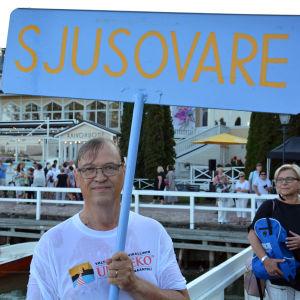 """Årets sjusovare 2018, Tapani Bastman, står i Nådendal med en stor blå skylt där det står """"Sjusovare"""""""