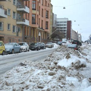 Stora snöhögar på en smal väg, flera bilar står parkerade längs vägen.