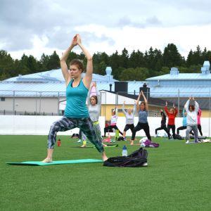 Många människor yogar med händerna i luften och fötterna brett.