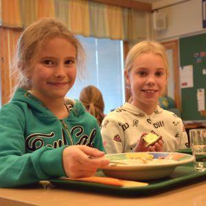 Eleverna Liv Svartsjö och Clara Åbrendt i Gerby skola äter lunch vid sina pulpeter.