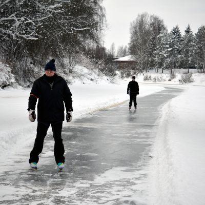Mies ja nainen luistelevat luistelureitillä joen jäällä.