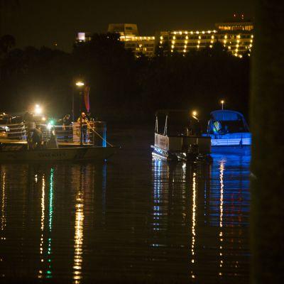 Pimeässä otetussa kuvassa näkyy vesillä olevia veneitä ja poliiseja. Taustalla näkyy kirkkaasti valaistu lomakeskuksen suuri hotellirakennus.