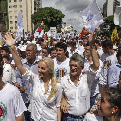 Valkoisiin pukeutuneita mielenosoittajia.
