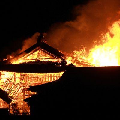 Eldslågor slår upp från det brinnande slottet Shuri på Okinawa