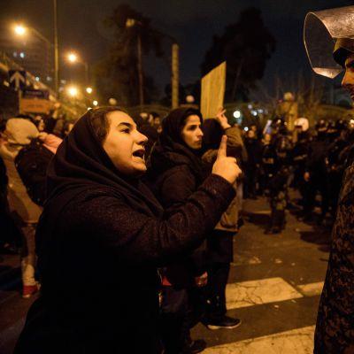 En kvinna talar med en polis i Teheran 11.1.2020 i samband med minnesstunder och demonstrationer