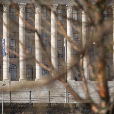eduskuntatalo nähtynä puun oksien takaa