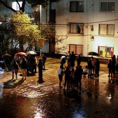I delar av Mexico City rusade människor ut i den regniga kvällen då byggnader började skaka.